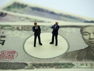 ミニチュアのビジネスマンとお金の写真素材 [FYI01262025]