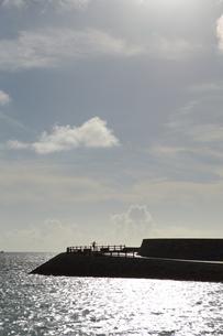 突堤で手を広げる人のシルエットの写真素材 [FYI01263061]