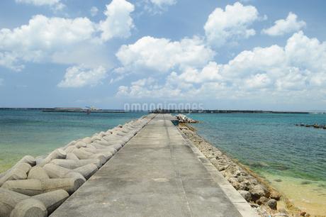 晴天の青空とエメラルドグリーンの海と防波堤の写真素材 [FYI01263345]