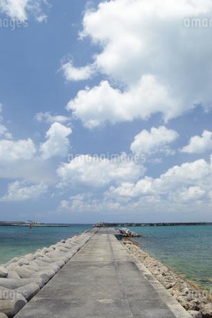 晴天の青空とエメラルドグリーンの海と防波堤の写真素材 [FYI01263346]