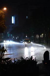 雨降りの都会の道路を車が通過するの写真素材 [FYI01263740]