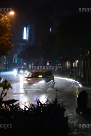 雨降りの都会の道路を車が通過するの写真素材 [FYI01263741]