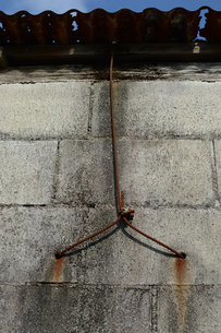 トタンとコンクリートブロックの壁を繋ぐ錆びたワイヤーの写真素材 [FYI01263934]