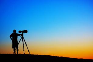 夕暮れの丘で写真を撮る男性の写真素材 [FYI01265145]