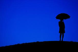 夜の丘に立つ傘をさす女性の写真素材 [FYI01265147]