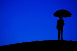 夜の丘に立つ傘をさす男性の写真素材 [FYI01265149]