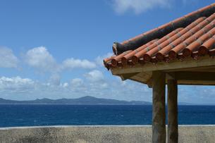晴天の青空と青い海と沖縄の赤瓦屋根の東屋の写真素材 [FYI01266486]