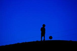 サッカーボールで遊ぶ少年(電線あり)の写真素材 [FYI01266872]