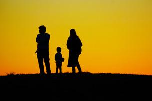 夕暮れの丘に立つ家族の写真素材 [FYI01266877]