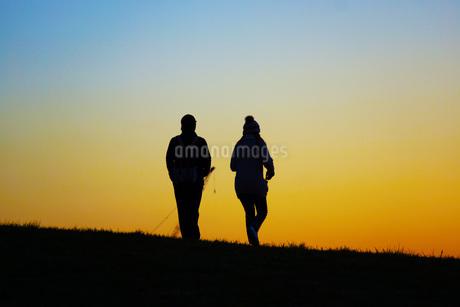 夕暮れの丘を歩く二人の写真素材 [FYI01266887]