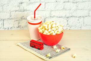 赤いボウルに入ったポップコーンと紙コップに入ったジュースの写真素材 [FYI01267141]