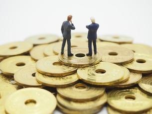 五円玉の上に乗るビジネスマンの写真素材 [FYI01267341]