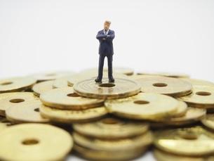 五円玉の上で腕組みするビジネスマンの写真素材 [FYI01267343]