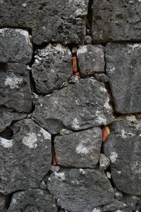沖縄の古い石垣の隙間に赤瓦のかけらの写真素材 [FYI01267409]