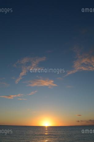 水平線に沈むオレンジ色の夕日の写真素材 [FYI01268434]