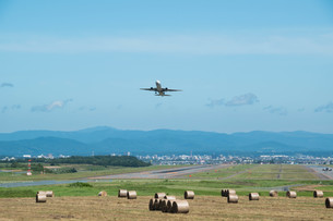 牧草ロールと離陸するジェット旅客機の写真素材 [FYI01268749]