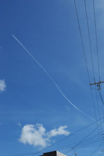 晴天の青空とゆがんだ飛行機雲の写真素材 [FYI01268871]