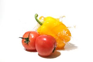 水しぶきを浴びるパプリカとトマトの写真素材 [FYI01268902]