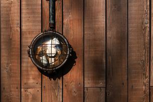 板張りの壁に取り付けられたレトロな電灯の写真素材 [FYI01269171]
