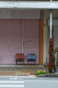 田舎の商店街のピンクのシャッターと椅子の写真素材 [FYI01269365]