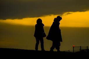 秋の夕暮の丘に立つ人々の写真素材 [FYI01269434]