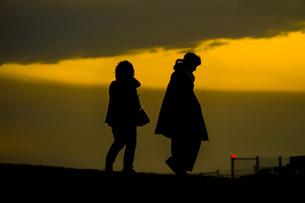 秋の夕暮の丘に立つ人々の写真素材 [FYI01269435]
