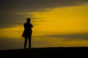 丘に立つ男性のシルエットの写真素材 [FYI01269436]
