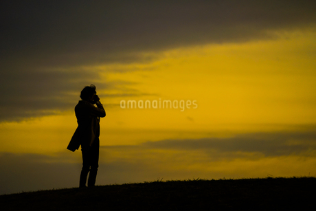 丘に立つ男性のシルエットの写真素材 [FYI01269437]
