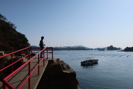 海岸沿いの参道にたたずむ男性と赤い手すりの写真素材 [FYI01272372]