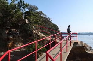 海岸沿いの参道にたたずむ男性と赤い手すりの写真素材 [FYI01272374]