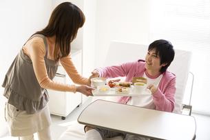 骨折した彼氏に病院食を運ぶ彼女の写真素材 [FYI01272884]