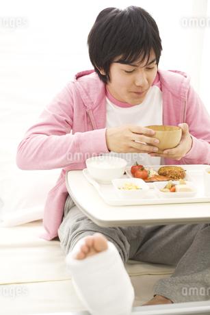 病院食を食べる骨折している男性の写真素材 [FYI01272885]