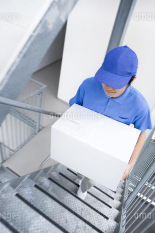 階段を上る配達員の男性の写真素材 [FYI01274244]