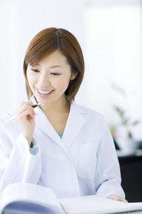 ペンを持つ白衣を着た女性の写真素材 [FYI01274366]