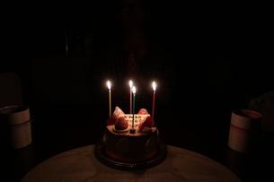 ろうそくがともった誕生日ケーキとマグカップの写真素材 [FYI01275528]