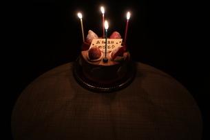 ろうそくがともった誕生日ケーキの写真素材 [FYI01275544]