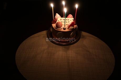 ろうそくがともった誕生日ケーキの写真素材 [FYI01275579]