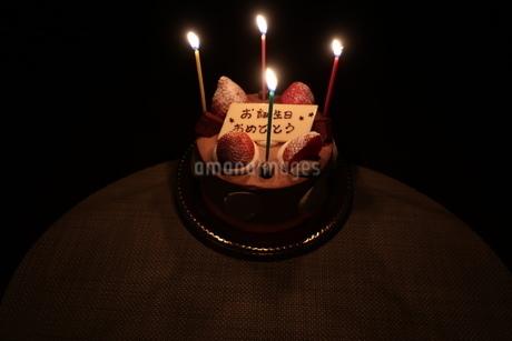 ろうそくがともった誕生日ケーキの写真素材 [FYI01275600]