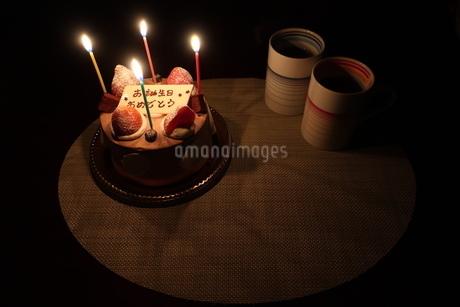 ろうそくがともった誕生日ケーキとマグカップの写真素材 [FYI01275650]