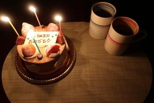 ろうそくがともった誕生日ケーキとマグカップの写真素材 [FYI01275685]
