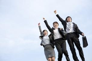 手を挙げてジャンプするビジネスマンとビジネスウーマンの写真素材 [FYI01275814]