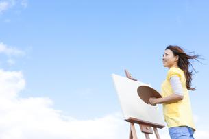 青空と絵を描く女性の写真素材 [FYI01276266]