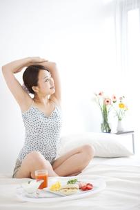 ベッドで伸びをする女性の写真素材 [FYI01276440]