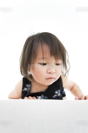 ソファからのぞき込んでいる女の子の写真素材 [FYI01276797]