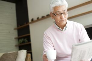 コーヒカップを持って新聞を読むシニア男性の写真素材 [FYI01276900]