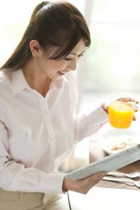 オレンジジュースを持って新聞を見ているビジネスウーマンの写真素材 [FYI01276949]