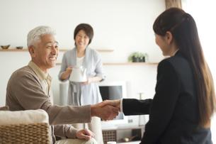 握手するビジネスウーマンとシニア夫婦の写真素材 [FYI01276950]