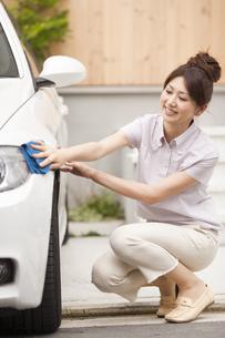 家の前で車を拭く若い女性の写真素材 [FYI01276991]