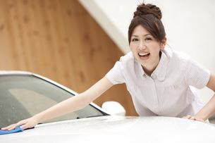 家の前で車を拭く若い女性の写真素材 [FYI01276993]
