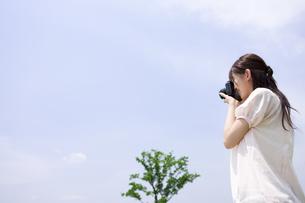 青空の下でカメラを構える女性の写真素材 [FYI01277265]